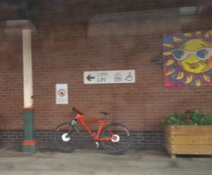 Orange bicycle standing on a station platform under a Welsh/English bilingual sign