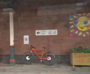 Orange bicycle standing on a station platform under a Welsh/English bilingual sign