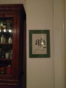 Framed calligraphed Chinese character hanging on a wall beside a cupboard