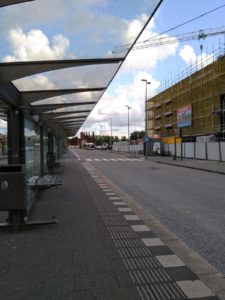 almost empty bus station under dramatic clouds