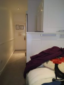 Small bright hotel room with single bed