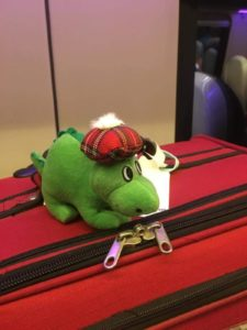 A small plush Nessie sitting on a large red suitcase