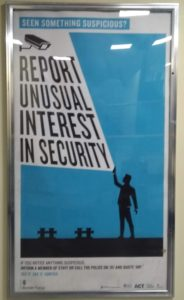 "Framed blue poster showing person with text balloon ""REPORT UNUSUAL INTEREST IN SECURITY"""