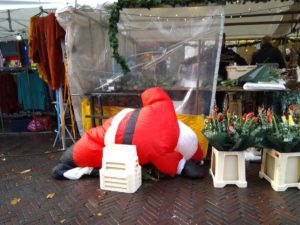 partly deflated inflatable Santa figure between market stalls